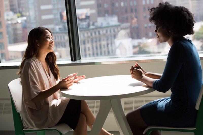 two_woman_sitting_talking