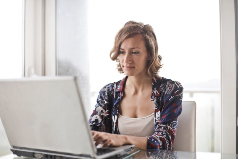 woman-in-blue-floral-top-sitting-while-using-laptop_