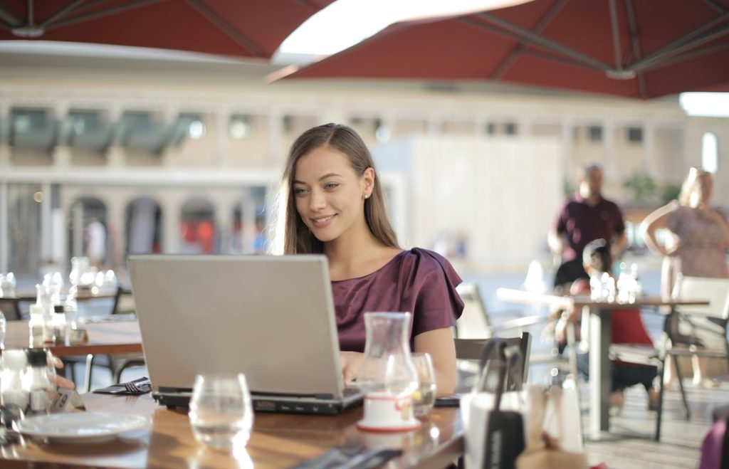 woman-in-purple-shirt-sitting-by-the-table-using-macbook