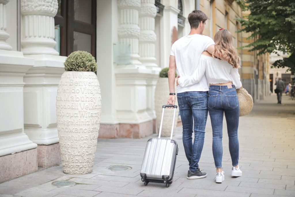 couple-with-suitcase-walking-along-city-street