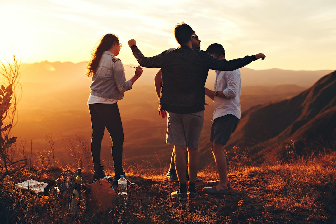 four-person-standing-at-top-of-grassy-mountain