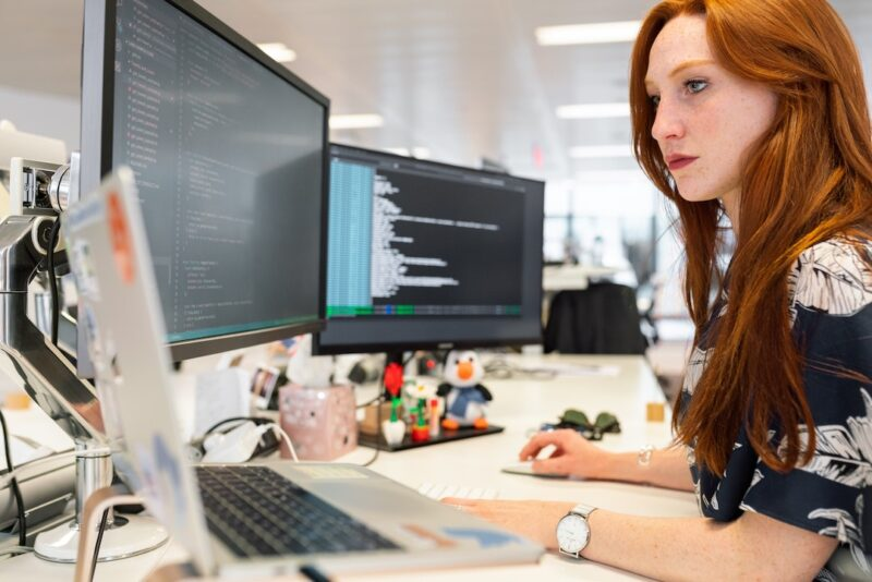 woman_sitting_in_front_of_three_monitors